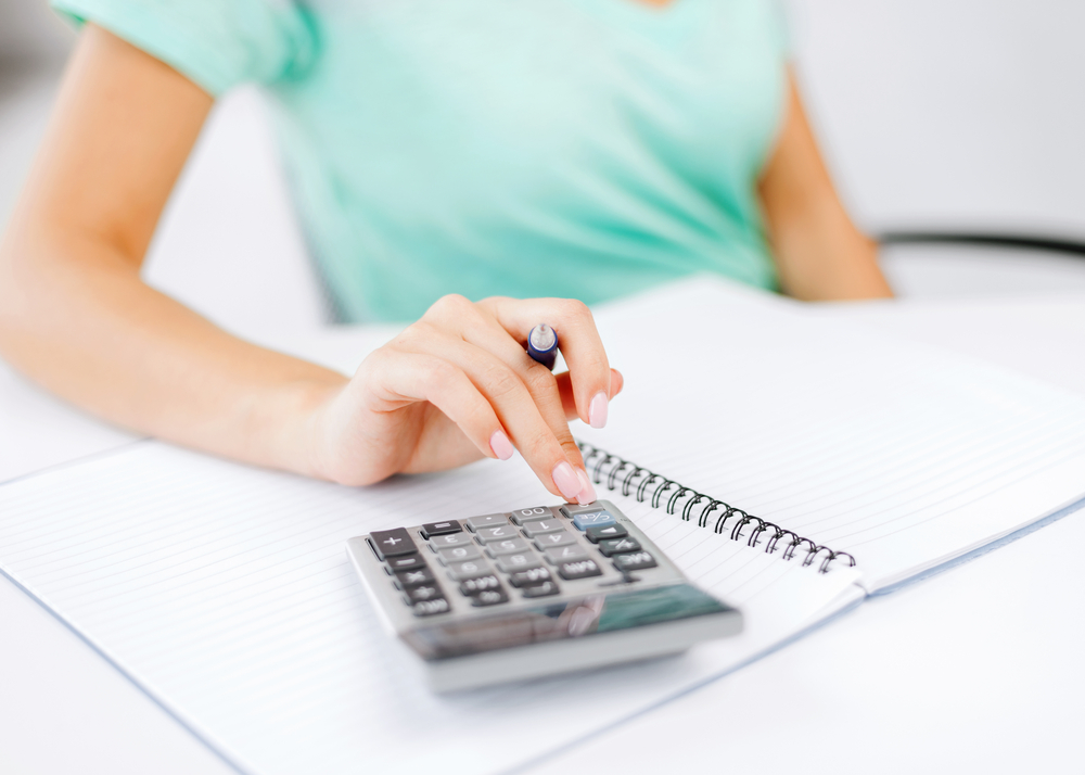 Image of lady with notepad and calculator doing a calculation