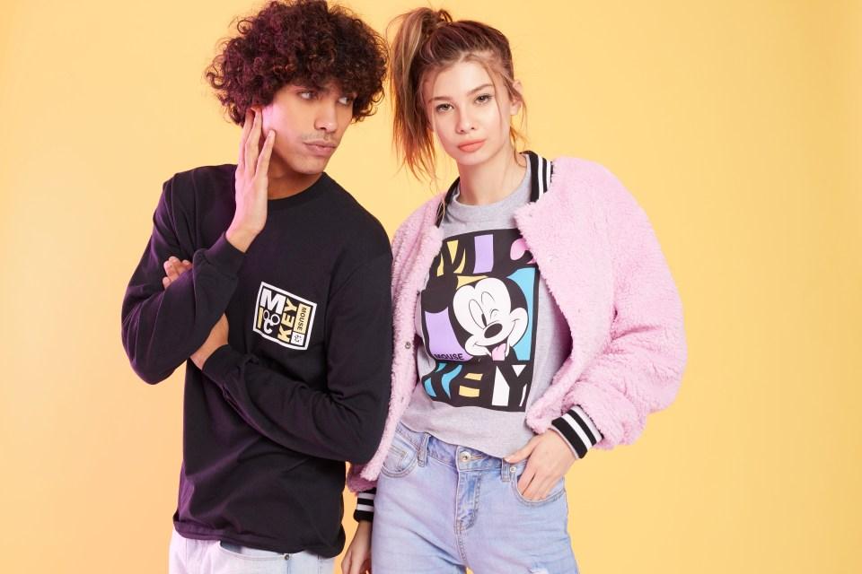 A male model wearing a long sleeve Mickey Mouse shirt, and a female model wearing a Mickey Mouse tee-shirt.