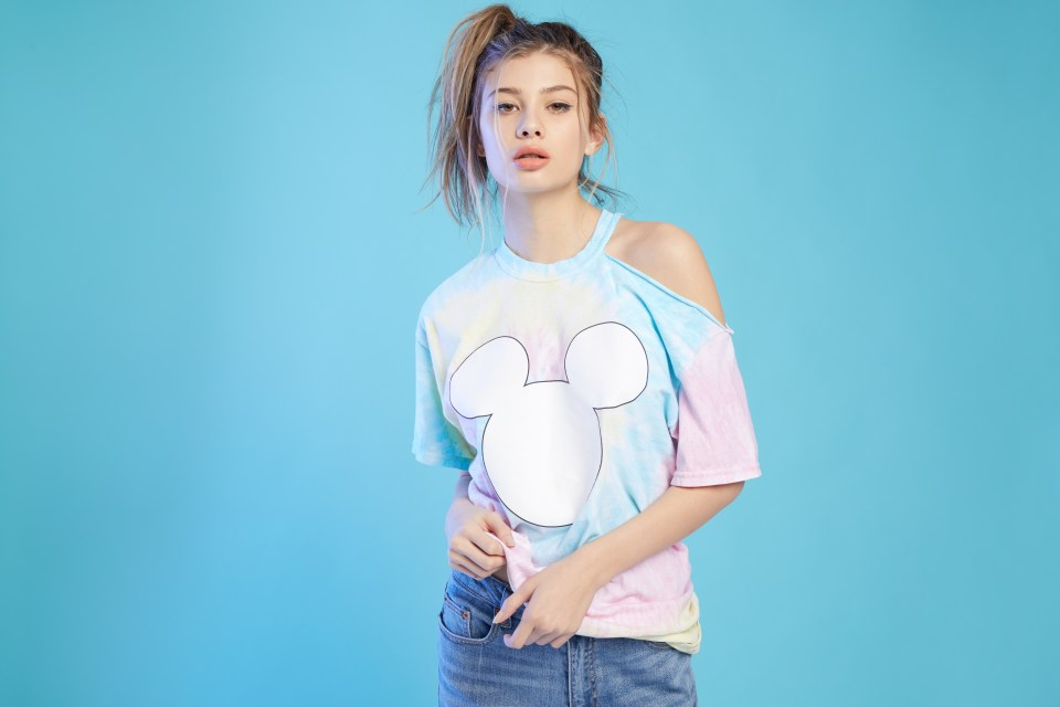 Female model wearing an off-shoulder Mickey Mouse shirt and jeans.