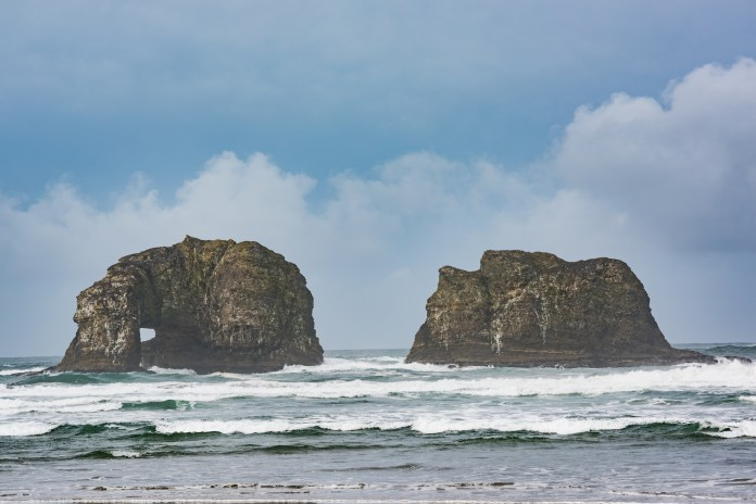 Twin Rocks in Rockaway Beach, Oregon during overcast, misty weather