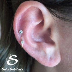 Double helxi piercing with jewelry by body vision los angeles