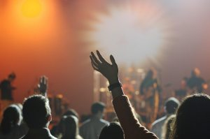 Person raising their hand in the air at a concert.