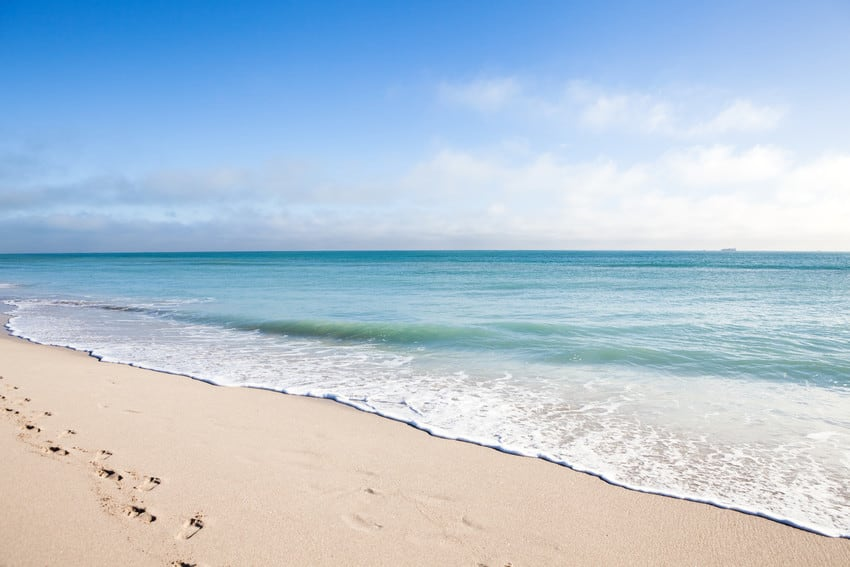 A Florida beach with footprints in the sand.