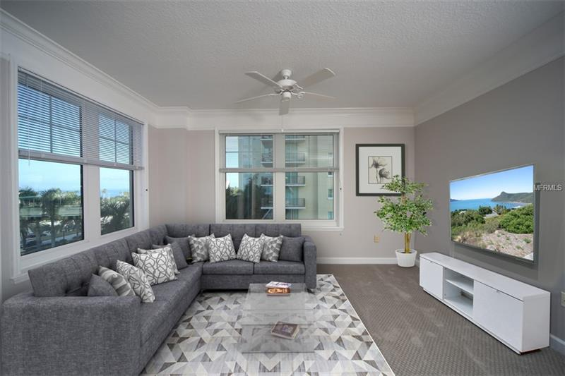 Staged living room area with sectional sofa, carpet, and television.