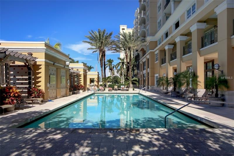 A stunning in-ground swimming pool flanked by impressive palm trees, beach chairs, and cabanas.