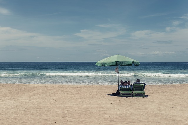 A couple of people relaxing on the beach underneath a green beach umbrella.