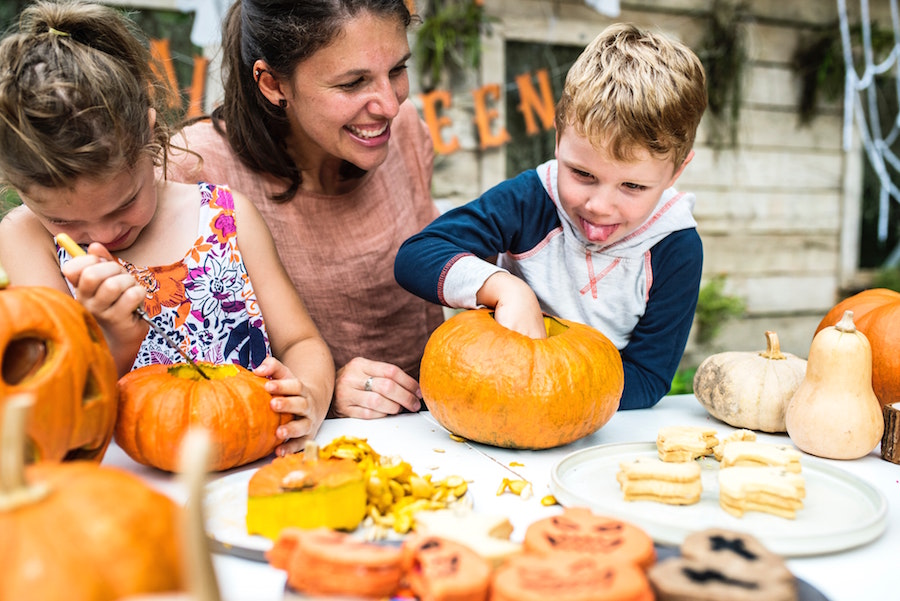 Woman and children carving pumpkins at one of Sarasota's fall festivals