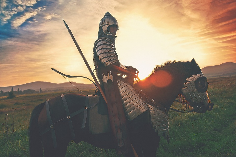 A knight in armor on a horse.
