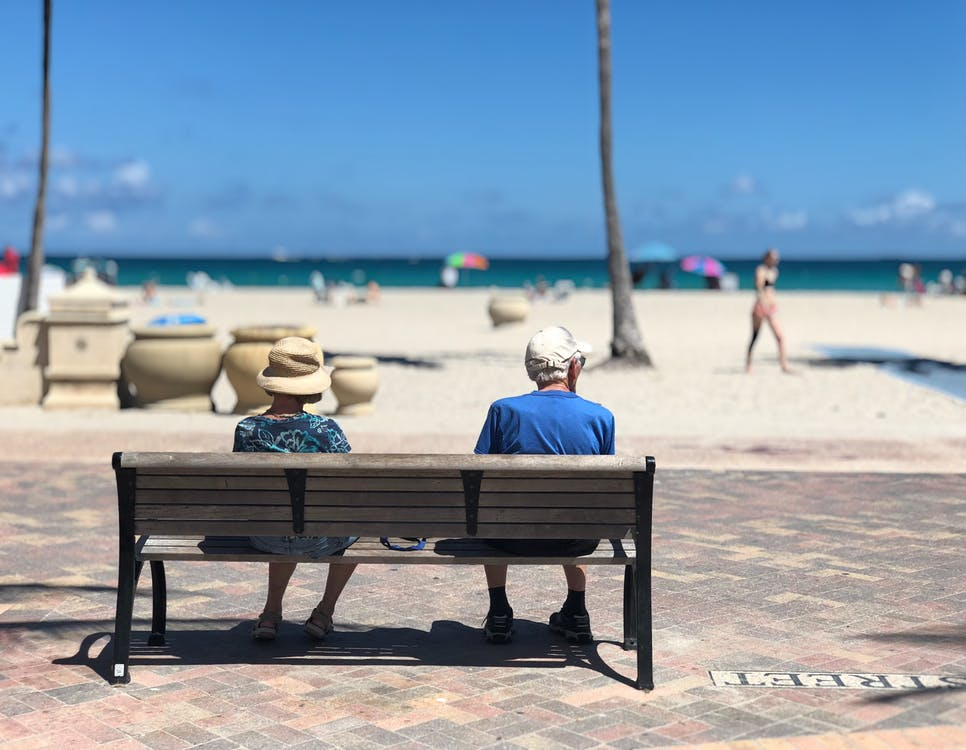 Two senior citizens sitting on a bench at the beach.