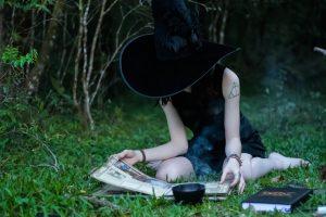 Chica con sombrero de bruja revisando unas notas