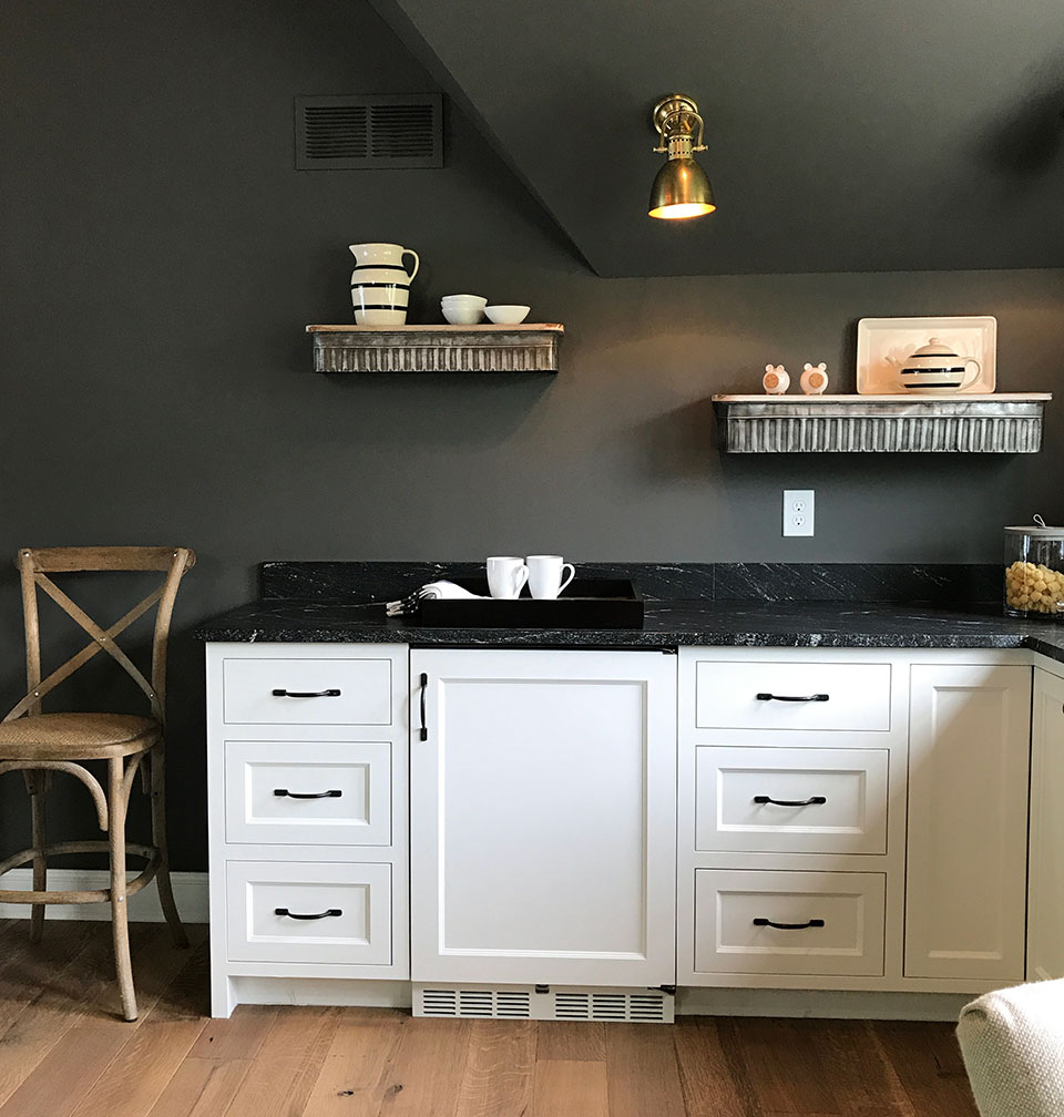 small kitchen with deep gray (charcoal) walls, white cabinets, black granite countertops, light wood floors, gold accents