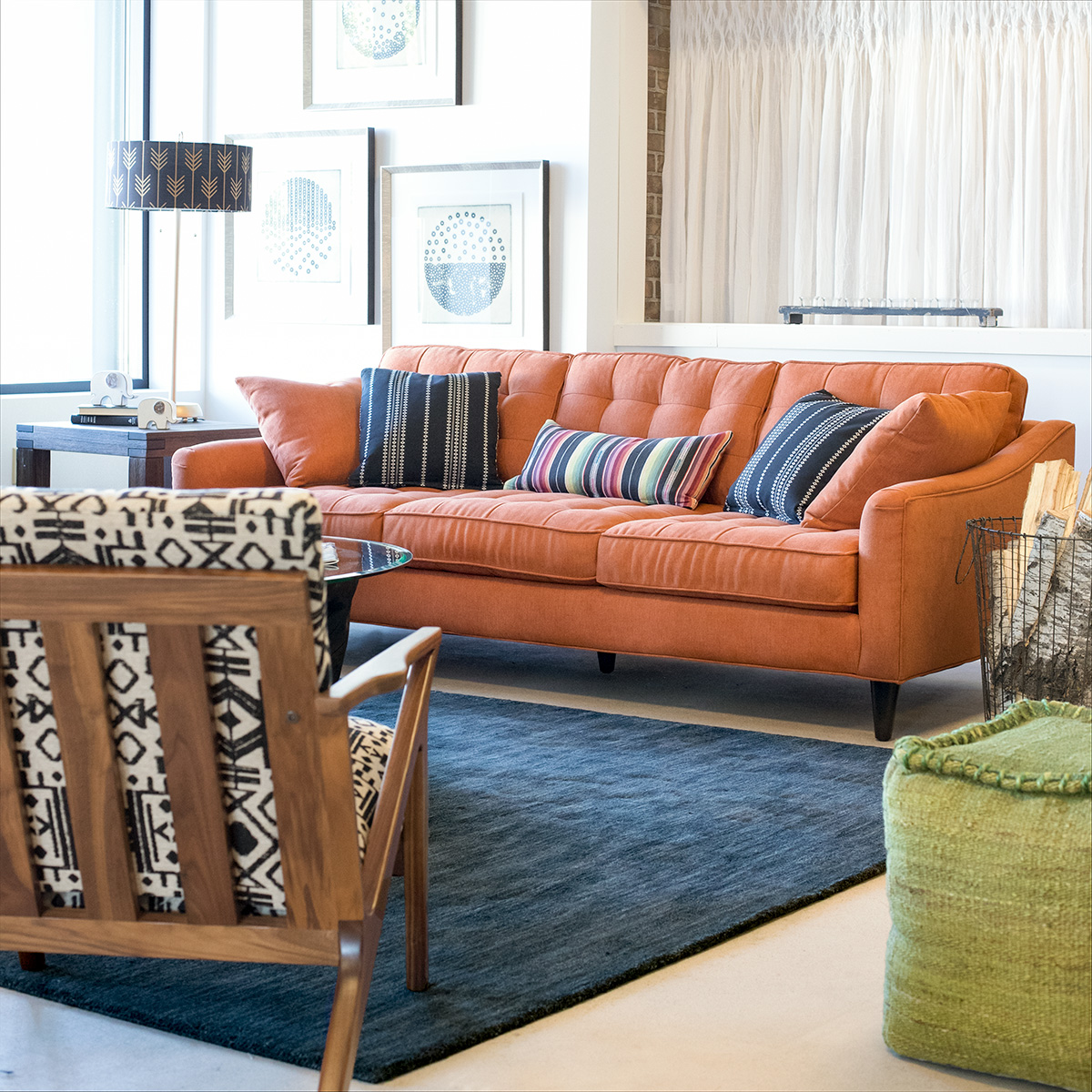 cheerful modern living room with orange mid-century sofa and exposed wood ethnic print chair.  Love this look - so fun!