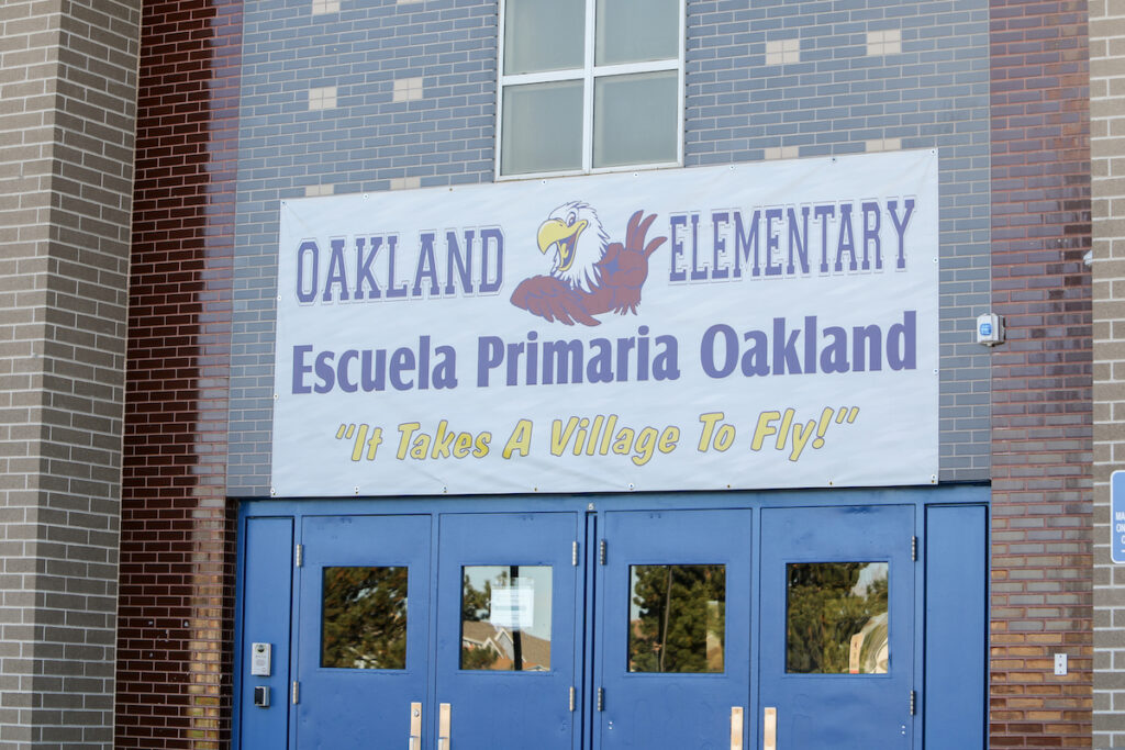 """The front doors of Oakland Elementary School, a top Denver school, according to SchoolSparrow rankings. A banner above the doors reads """"It takes a village to fly!"""""""