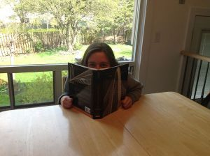 woman sitting at a table peering over a textbook