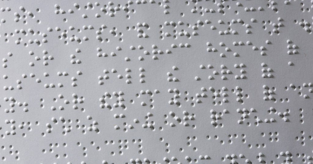 A close-up of Braille text inside the Wolf Handbook for Cub Scouts.