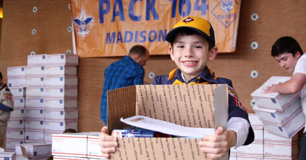 Every year, this pack gathers to assemble Christmas care packages for the troops