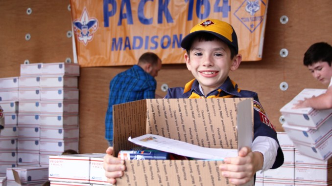 Cub Scout holding care package.