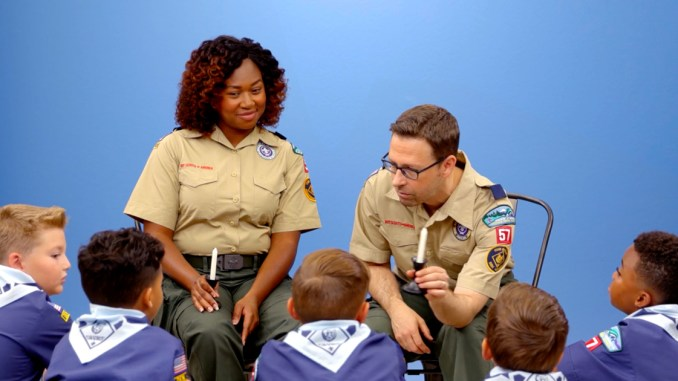 Two Cub Scouts leaders talking to a group of Cub Scouts