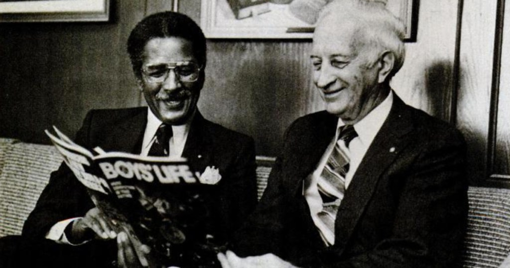 Joseph Merton reads Boys' Life magazine with J.L. Tarr, the BSA's seventh Chief Scout Executive.