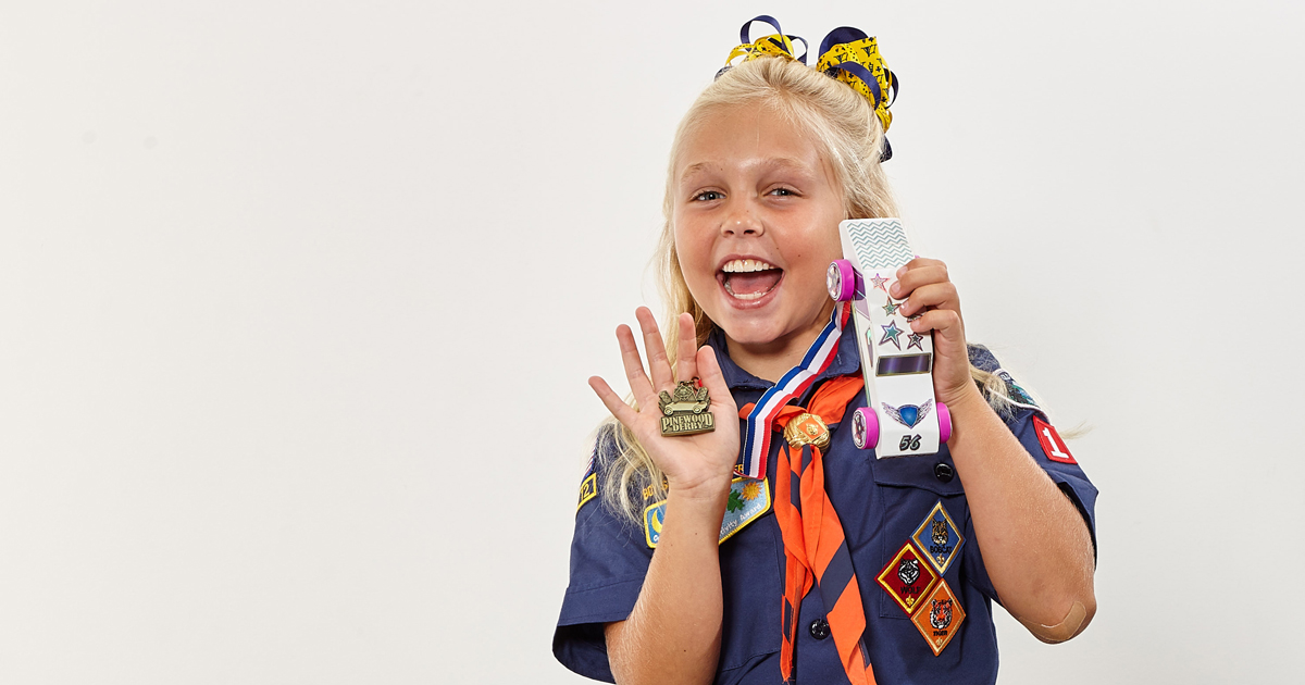 Female Cub Scout holds Pinewood Derby car and medal