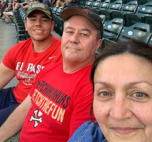 Andrew with his parents at a baseball game.