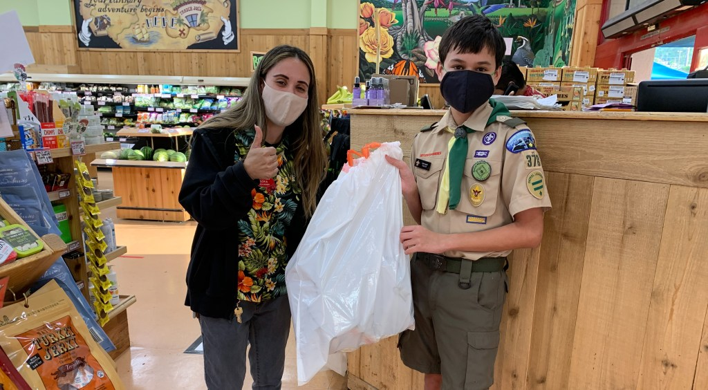First Class Scout Sam Lovall delivers face shields to grocery workers.
