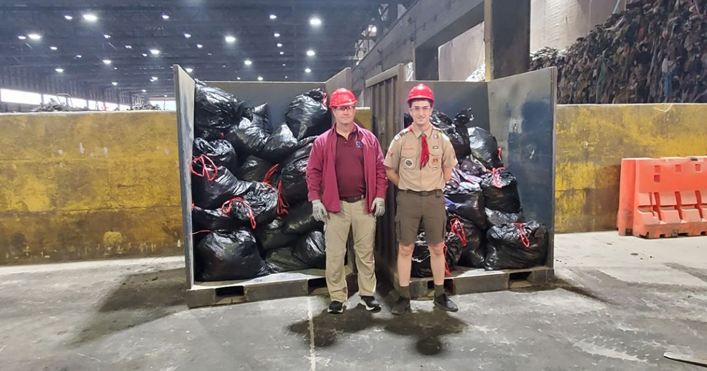 David (left) and Thomas Byrne stand by as workers prepare to retire by incineration thousands of torn and tattered flags. (Photo courtesy of Prince William County Solid Waste Division)