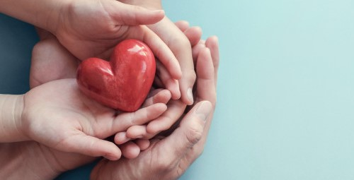 adult-child-hands-holding-red-heart-aqua-background_49149-944