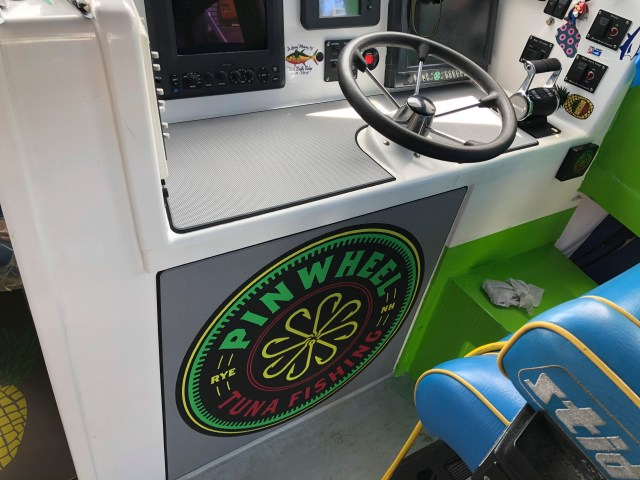 The helm and cock pit area of the pinwheel boat featuring the pinwheel logo.