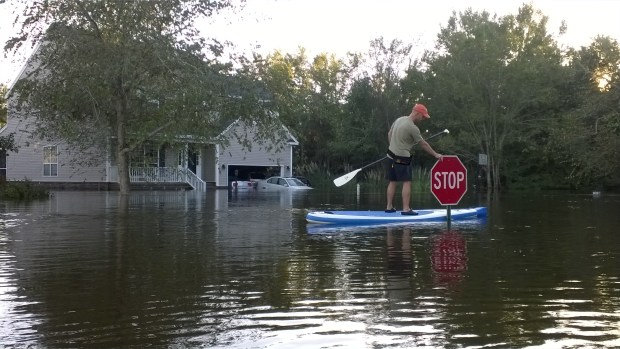 "Wilfred Baker rides his Sea Eagle Needlenose™ SUP through their neighborhood during a recent flood in Summerville, SC. ""A surreal experience,"" says his wife, Wendy."