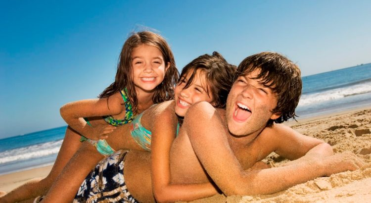 three kids in a pile on the sand at the beach