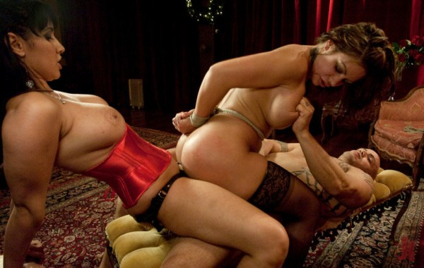 Lustful brunette is being fucked by a man in her pussy and by a woman in strap-on in her ass