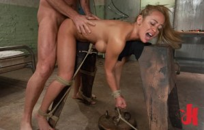 Blonde, lustful whore gets fucked from behind by a dominating man while tied to an iron horse