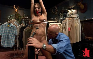 Submissive whore with a hanger clinging to her nipples has a ball gag in her mouth and is teased