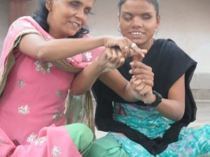 Two young VI women smiling and making the letter T with their hands.
