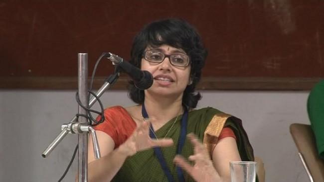 A photo of Amba Salelkar speaking into a microphone.