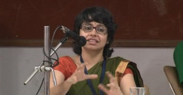 A photo of Amba Salelkar speaking into a microphone.