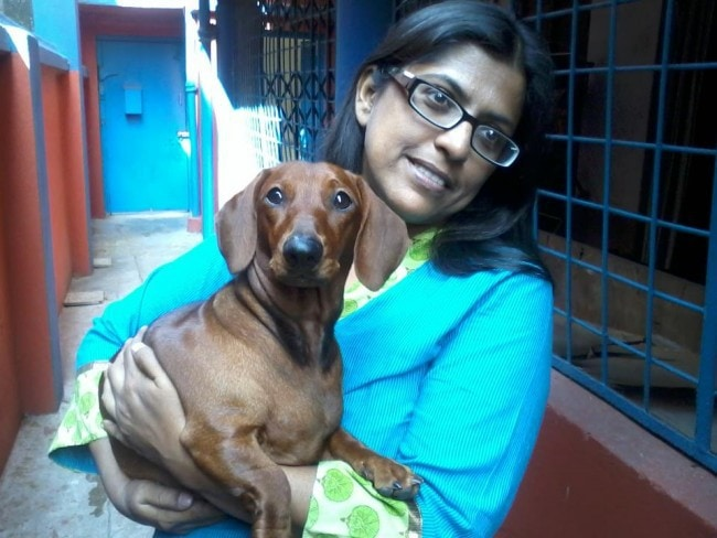 A photo of Shampa Sengupta holding a small brown dog in her arms.