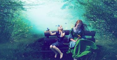 A digital picture of a woman and a girl sitting together from Wallpaperup.com. In the background there is a forest. The centre of it is lit up. In the foreground, a little girl is sitting on a wooden bench looking happily at butterflies flying above her. Next to her sits a woman looking a little sad. She is looking down at a yellow flower in her hand.