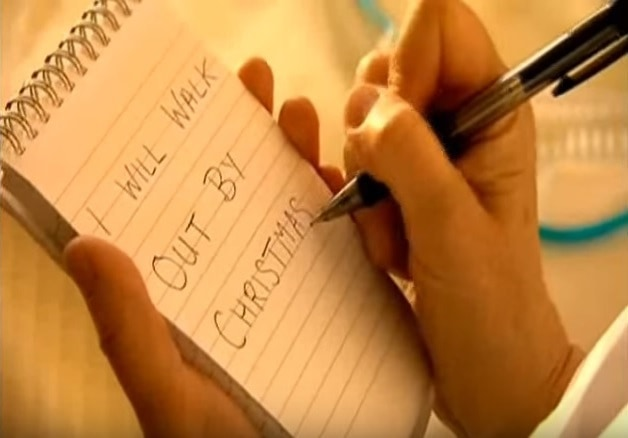 "A photo from Morris E. Goodman's The Miracle Man. A close up of a notebook and pen with the words ""I will walk out by Christmas"" written on the notepad."