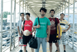 A still from Tu Hai Mera Sunday, showing five young men facing the camera in formation. The one on the furthest left corner is wearing a grey shirt and smiling awkwardly, the one next to him is wearing a 'Fly Emirates' shirt and holding a football, the one on the centre is wearing a green tee shirt that says 'Be Yourself' and holding a black bag, the one to his immediate right is wearing a maroon tee shirt and grinning, and the one on the extreme right is wearing a yellow and black striped shirt, with his hand on his waist.