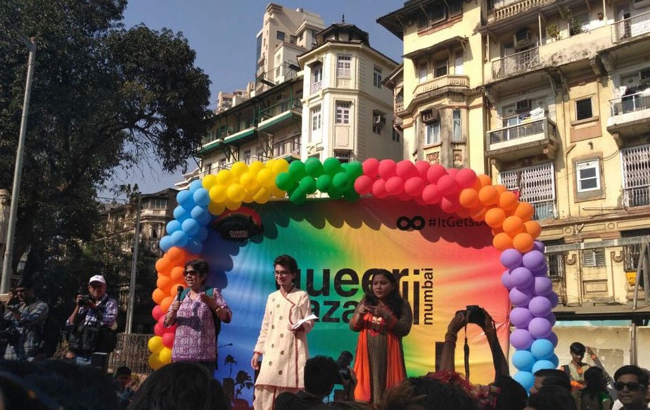 The photograph shows the stage of the Queer Azaadi Mumbai Pride March, 2017. There are three people standing on the stage. One person is speaking on the microphone, with the second person smiling as the third person interprets what is being said in sign language. The backdrop of the stage is decorated with rainbow-coloured balloons.