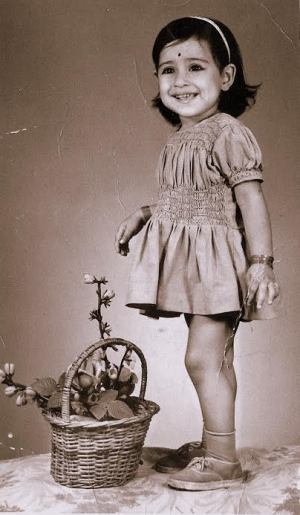 In this sepia toned photograph of Abha as a little girl, she is wearing a frock with socks and shoes along with a hair band and a bindi on her forehead. She wears a wide smile as she poses for the photograph. Next to her is a woven flower basket with flowers in it.