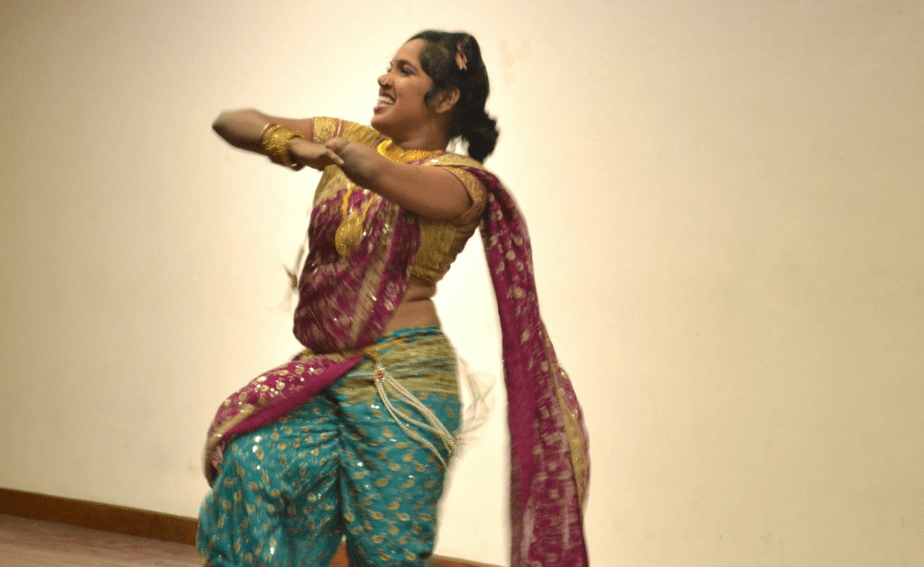 The photograph shows a woman wearing a pink and turquoise navari sari with golden work and a golden blouse. She is performing a lavani on stage.