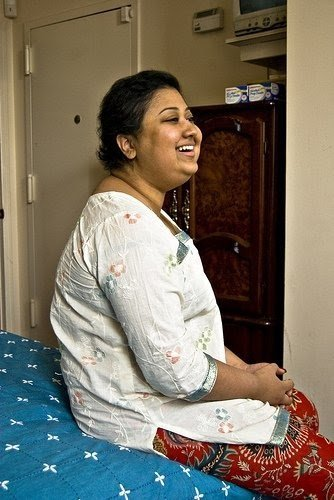 A young woman dressed in a white kurta is sitting on a bed. She has smiling and has close cropped hair.