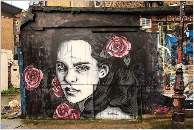 This photograph shows a mural of a woman with dark hair painted on a wall. She looks confidently and almost directly in the direction of the camera. She has several large dark pink roses in her hair and vicinity.