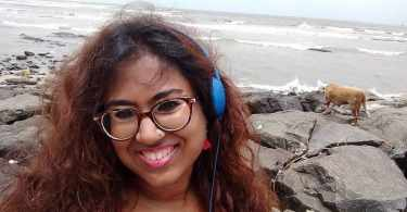In this picture of Durga, she is smiling, and wearing a pink top and blue headphones. In the background, there is the sea, and to her right, a small brown dog sniffs around therocks.