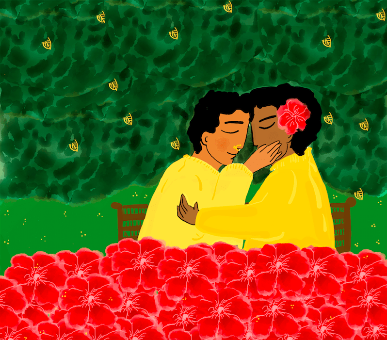 Description: Two people sit on a bench, facing each other, eyes closed, foreheads touching, as they embrace. They both wear yellow and have short hair. One wears a nose ring, the other has a flower in their hair. In the background we see a dense canopy of green leaves and, at the bottom, a bed of bright red flowers.