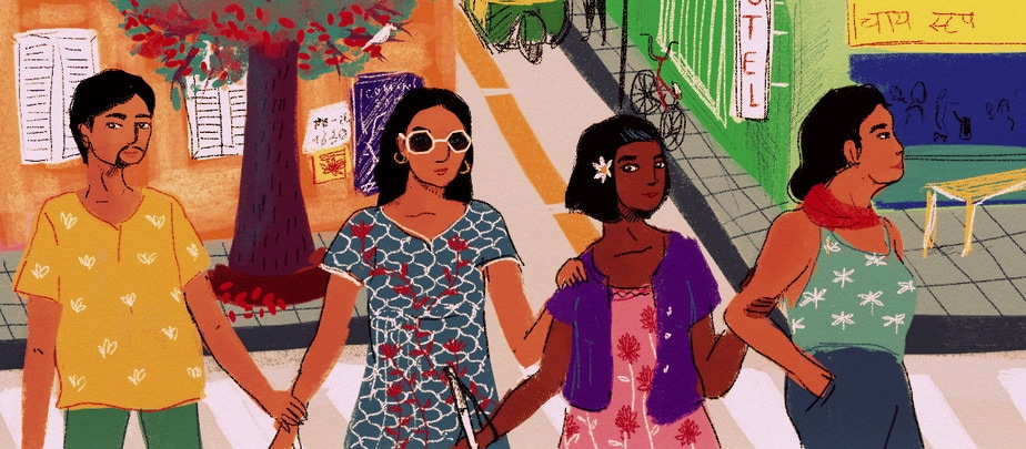 Four people stand in a row, holding each other's shoulders or arms. One has a beard, another wears sunglasses and another holds a white cane. Behind them, a road and footpath with a bike, tree and shops.