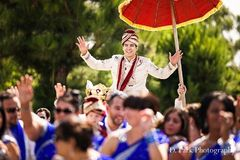 Groom having a good time dancing mounted on a horse for his Indian wedding baraat